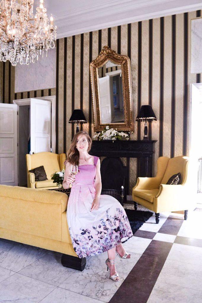 Weingenießerin auf gelben Sofa in Huis de Voogst